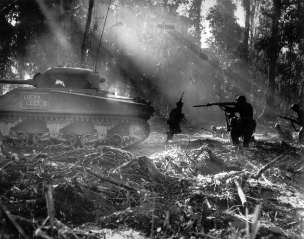 March 1944: Following in the cover of a tank, American infantrymen secure an area on Bougainville, Solomon Islands after Japanese forces infiltrated their lines during the night.