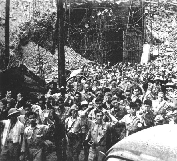 May 1942: After defending the island for nearly a month, American and Filipino soldiers surrender to Japanese invasion troops on Corregidor island, Philippines. This photograph was captured from the Japanese during Japan's three-year occupation.