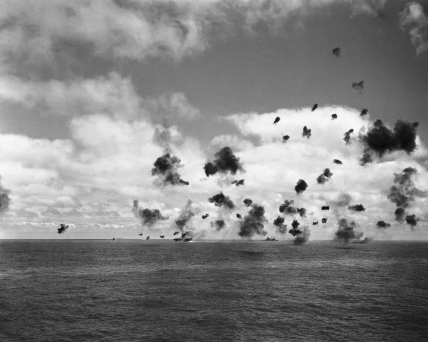 June 4, 1942: The U.S. aircraft carrier Yorktown, left, and the other fighting ships of a United States task force in the Pacific, throw up an umbrella of anti-aircraft fire to beat off a squadron of Japanese torpedo planes attacking the carrier during the battle of Midway.