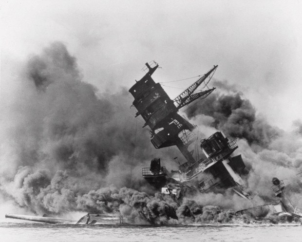 "December 7, 1941: The battleship USS Arizona belches smoke as it topples over into the sea during a Japanese surprise attack on Pearl Harbor, Hawaii. The ship sank with more than 80 percent of its 1,500-man crew. The attack, which left 2,343 Americans dead and 916 missing, broke the backbone of the U.S. Pacific Fleet and forced America out of a policy of isolationism. President Franklin D. Roosevelt announced that it was ""a date which will live in infamy"" and Congress declared war on Japan the morning after."