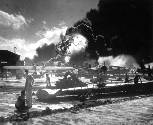 December 7, 1941: Sailors stand among wrecked airplanes at Ford Island Naval Air Station as they watch the explosion of the USS Shaw in the background, during the Japanese surprise attack on Pearl Harbor, Hawaii.