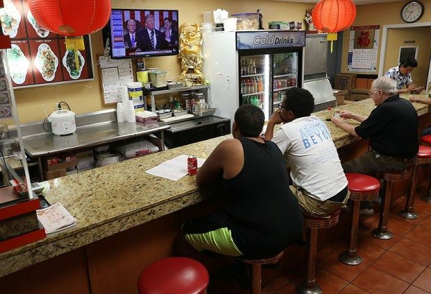 Customers at a Chinese restaurant in Miami watch television Tuesday night as President Donald Trump delivers a speech to a joint session of the U.S. Congress.
