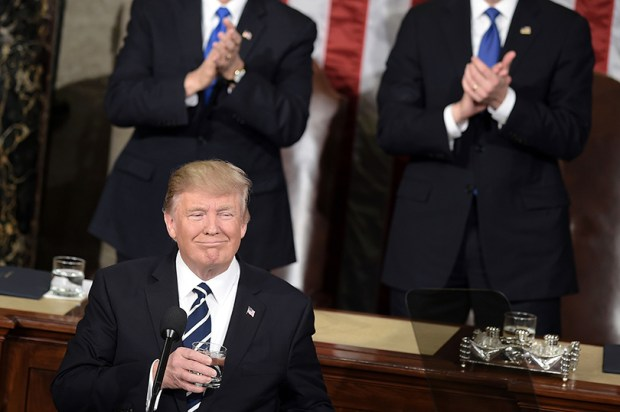 President Donald Trump pauses for applause while speaking before a joint session of Congress on the floor of the House on Tuesday in Washington.