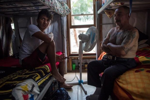 Migrants Juan Parras, 65, right, and ...