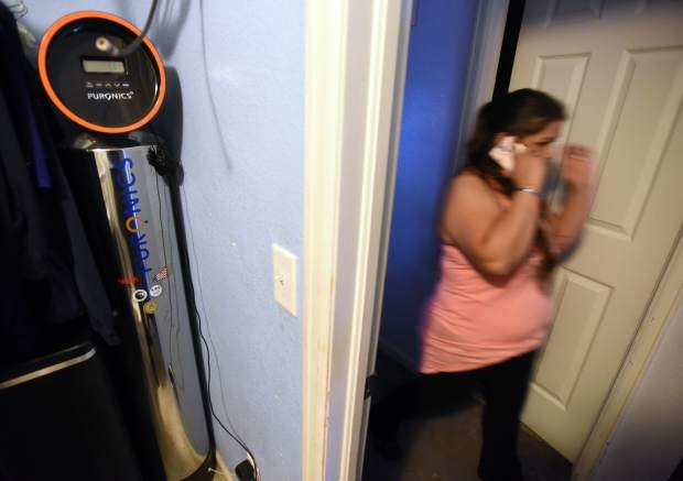 A soft water system sits in a closet as Esther Martinez walks past while in her home Wednesday in Greeley. The systems cost $7,500, but the family will pay about $3,000 in interest because they financed through the company that sold the systems.