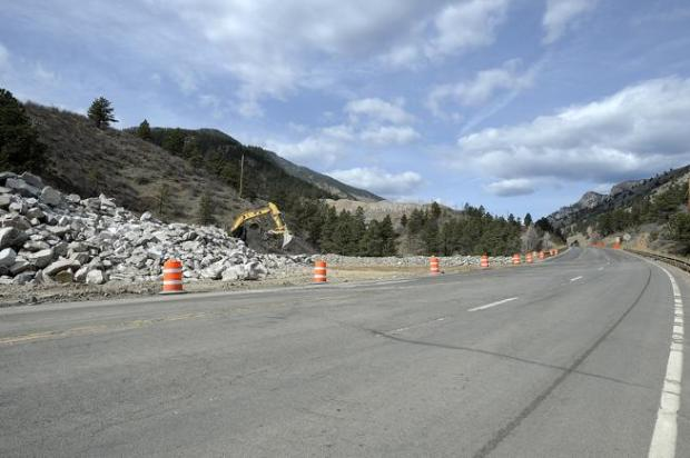 Crews use heavy equipment to spread large rocks and boulders, from blasting along the highway March 17 on property owned by the city of Loveland at Round Mountain along U.S. 34 in the Big Thompson Canyon west of Loveland. Colorado Department of Transportation is leasing the space from the city until permanent repairs to U.S. 34 are complete.