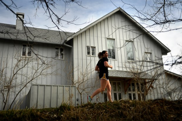 A woman runs along the Cherry Creek Trail in Denver.