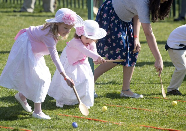 Two young girls race with eggs and spoons during the White House Easter Egg Roll on the South Lawn of the White House on April 1, 2013.