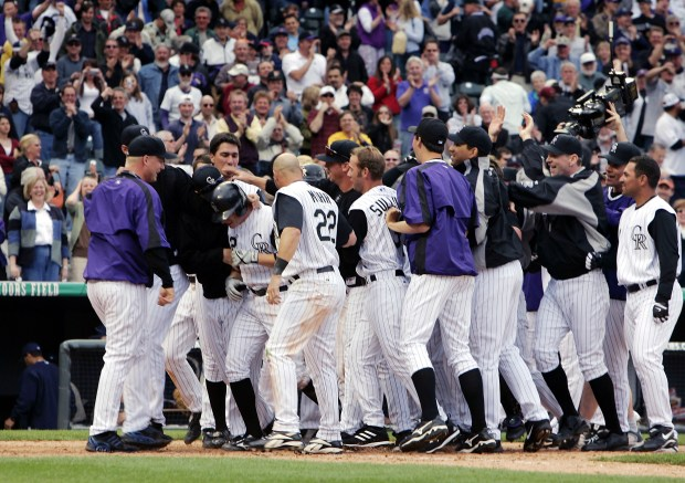 DENVER - APRIL 4: Clint Barmes #12 of the Colorado Rockies is swarmed by his teammates after hitting a walk-off game-winning home run against the San Diego Padres in the bottom of the ninth inning at Coors Field on opening day on April 4, 2005 in Denver, Colorado. The Rockies won 12-10. (Photo by Brian Bahr/Getty Images)