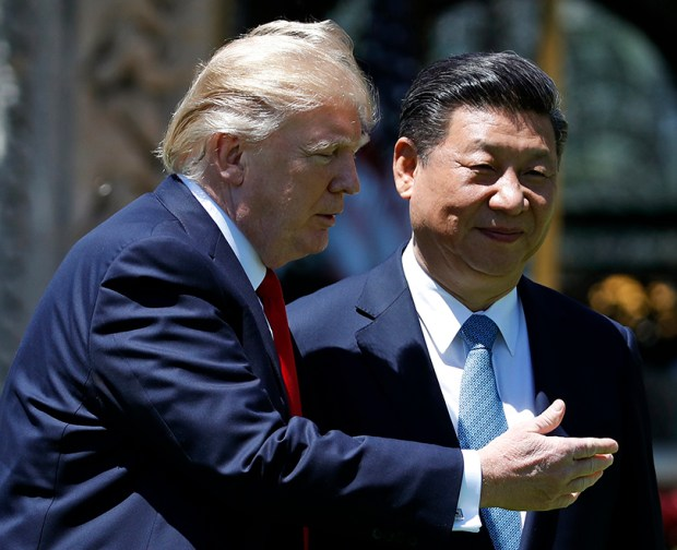 President Donald Trump and Chinese President Xi Jinping walk together after their meetings at the Mar-a-Lago resort in Palm Beach, Fla., on April 7.