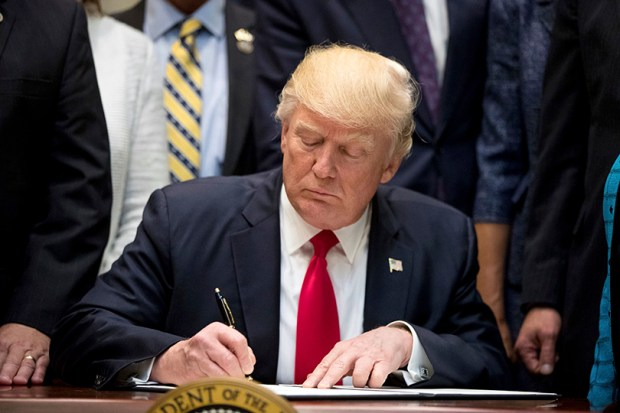 President Donald Trump signs an executive order on Wednesday in the Oval Office.