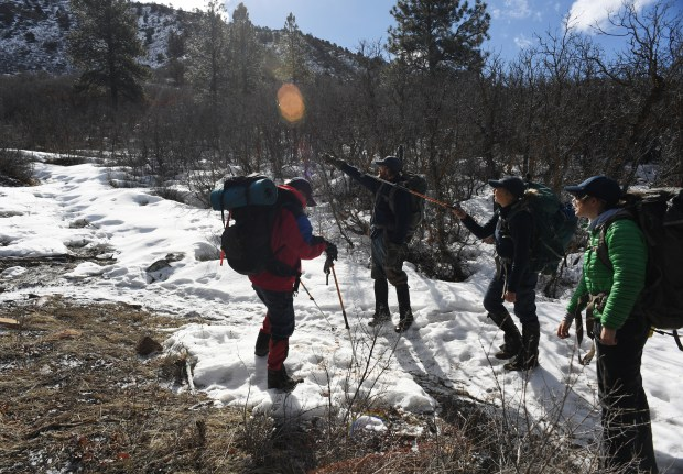 Colorado Parks and Wildlife researchers plan their hike up Raider Ridge to a bear den.