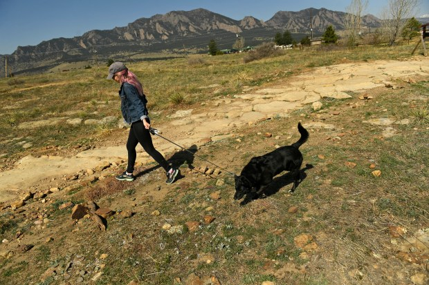 A woman who did not want to be identified walks with her dog Angel on the trails at Marshall Mesa open space on April 13, 2017 in Boulder. Marshall Mesa is part of the City of Boulder's Voice and Sight Tag program where dogs can be off leash if they have the requisite yearly tag.