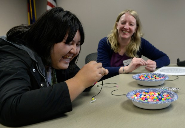 Jenny Butler, right, library staff, joins Candy Khukhu as she threads beads into a bracelet at the Golden Library on March 30.