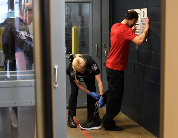 Denver Sheriff's Deputies process an inmate ...