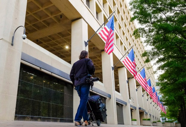 A member of the news media walks in front of the FBI headquarters building on Wednesday, a day after President Donald Trump fired FBI Director James Comey.