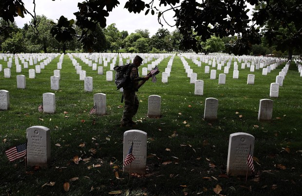 Members of the 3rd U.S. Infantry Regiment place flags at the headstones of U.S. military personnel buried at Arlington National Cemetery on Thursday in preparation for Memorial Day.