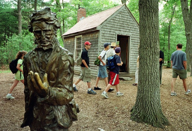 "A group of students walks past a bronze statue of author Henry David Thoreau near a replica of the author's house at the Walden Pond State Reservation in Concord, Mass., on July 12, 2001. In his most popular work, ""Walden,"" Thoreau wrote: ""I went to the woods because I wished to live deliberately, to front only the essential facts of life, and see if I could not learn what it had to teach, and not, when I came to die, discover that I had not lived."""