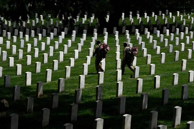 Two members of the U.S. Army walk past gravestones as they prepare to place American flags on graves at Arlington National Cemetery on Thursday in preparation for Memorial Day.