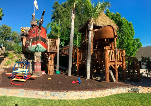 Two custom playhouses built by Daniels Wood Land sit in the Caster's yard in San Diego, Calif. The pirate ship and Swiss Family Robinson-inspired treehouses are built on recycled treestumps and connected by a rope bridge.