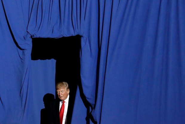 President Donald Trump walks from behind a curtain as he is introduced at a rally in Harrisburg, Pa., on April 29.