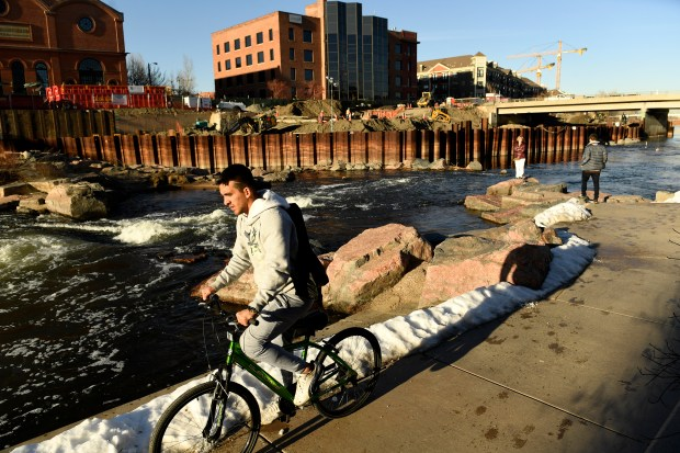 Victor Saucedo rides his bike across the river where work continues at the riverfront plaza at Confluence Park on December 29, 2016 in Denver.