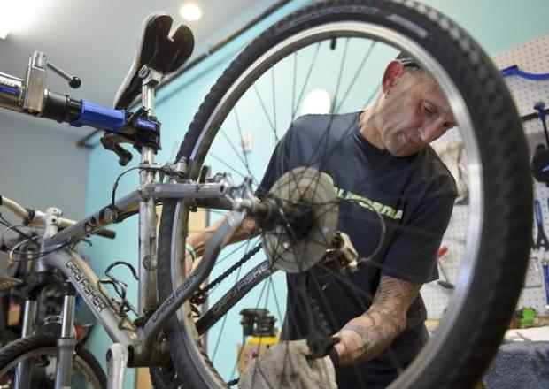 Longmont Velo bike shop owner Paul Anderson works on a bike on May 18, 2017 that will be given to a HOPE client.a