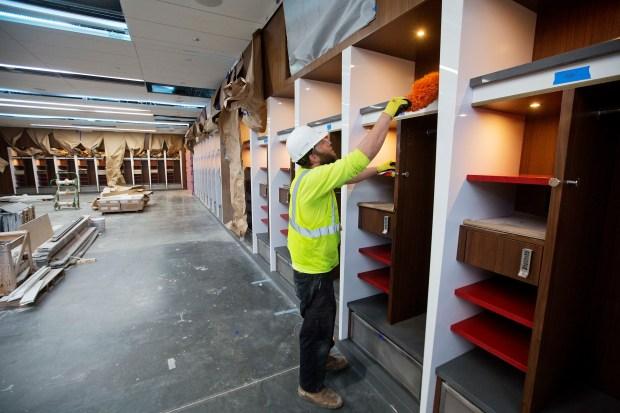 A worker dusts off a shelf ...