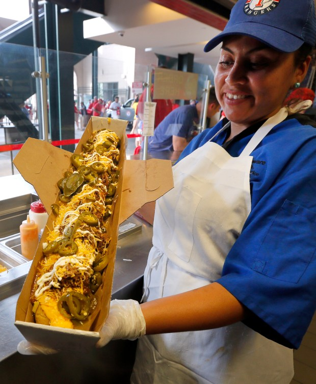 Fabiola Bolanos shows off a freshly made Most Valuable Tamale before a baseball game between the Los Angeles Angels and the Texas Rangers in Arlington, Texas, Friday, April 28, 2017. The 24-inch tamale is filled with the boomstick hot dog, and topped with Texas chili, nacho cheese, sour cream and jalapenos. (AP Photo/Tony Gutierrez)