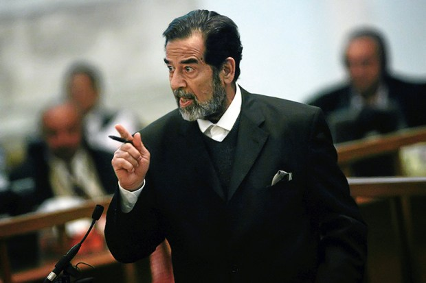 Former Iraqi leader Saddam Hussein gestures during his trial in Baghdad on Oct. 10, 2006.