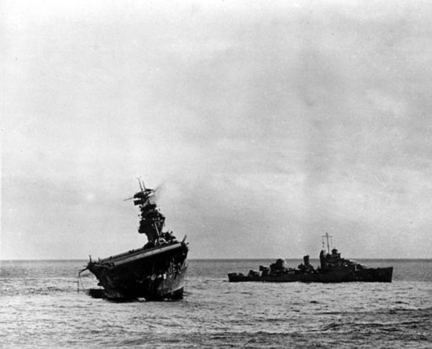 In this June 1942 file photo, the USS Yorktown lists heavily to port after being struck by Japanese bombers and torpedo planes in the Battle of Midway during World War II, as a destroyer stands by at right to assist as a salvage crew on the flight deck tries to right the stricken aircraft carrier.