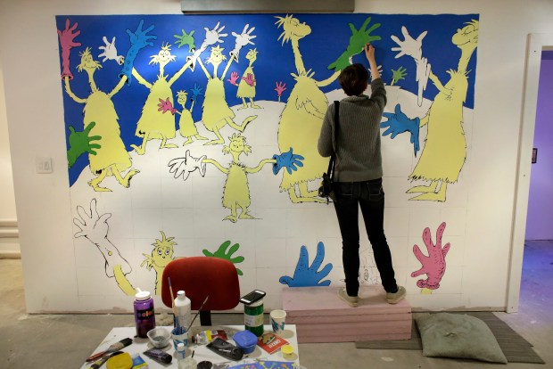 """Cortney Thibodeau paints a mural based on artwork from the Dr. Seuss book """"Oh, The Thinks You Can Think!"""" at The Amazing World of Dr. Seuss Museum, in Springfield, Mass."""