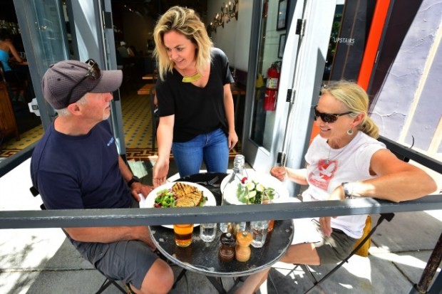 General Manager Andrea Oloughlin checks in with customers John and Debra Lanzl as she delivers their lunch at The Kitchen in Boulder on Wednesday. The two are celebrating their 40th anniversary and visiting Boulder from Connecticut.