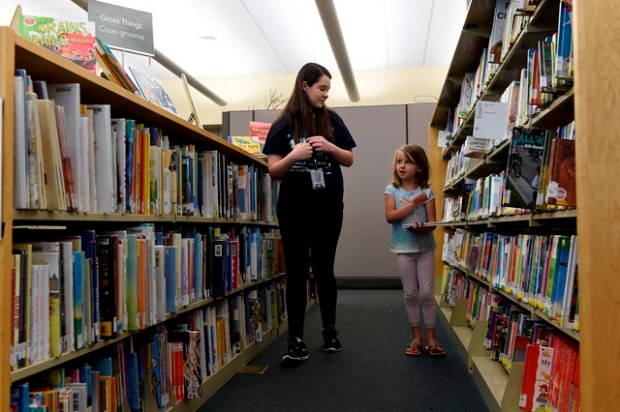 Emilie Matthews helps Maddison Morgan, 5, pick out a book during the ReadingBuddies program at Belmar Library on June 6.