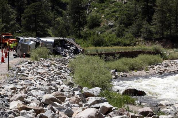 A semitruck turned flipped on its side and spilled trash along the Big Thompson River on U.S. 34 in the Big Thompson Canyon on Wednesday.