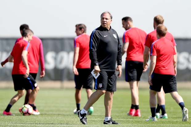 Head coach Bruce Arena walks on ...