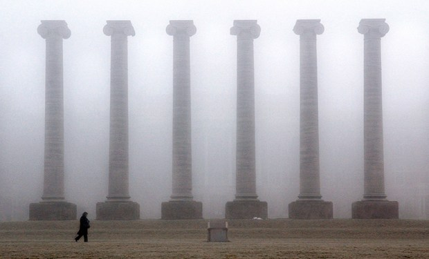 A woman walks near columns shrouded in fog on Feb. 3, 2005, on the University of Missouri-Columbia campus in Columbia, Mo. Freshman enrollment at Missouri has fallen by more than 35 percent since protests in November 2015.