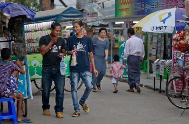 In this April 11, 2017 photo, former enslaved fishermen Phyo Kyaw, center right, and Win Ko Naing, center left, walk in a Yangon street, Myanmar. After Kyaw was rescued from Benjina, he worked for a few months on the gritty outskirts of Yangon as a motorbike taxi driver, but the money wasn't good and his bike soon got stolen.
