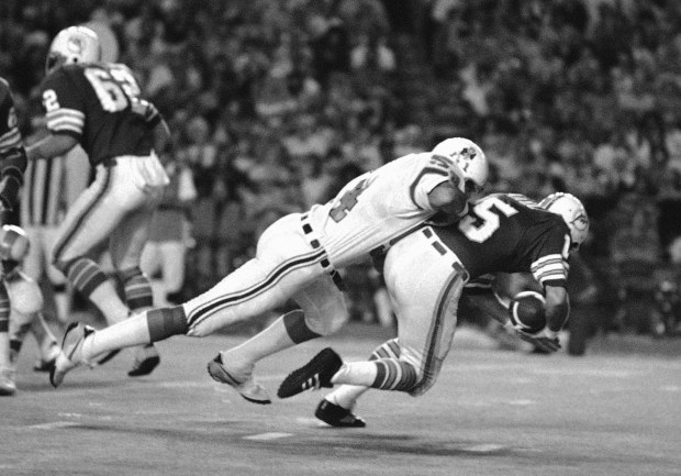 In this Dec. 2, 1975, file photo, Miami Dolphins quarterback Earl Morrall is tackled by New England Patriots linebacker Steve Zabel during a football game in Miami. This week, The Associated Press interviewed the surviving relatives of more than a dozen players involved in a study about living and dying with CTE.