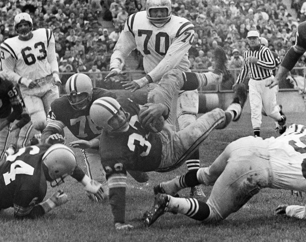 In this Oct. 11, 1959, file photo, Green Bay Packers halfback Lewis Carpenter (33) is upended by San Francisco 49ers Matt Hazeltine (55) in the second quarter of an NFL football game in Green Bay, Wis. A running back who won three NFL championships in a 10-year career with the Lions, Browns and Packers, Carpenter stuck around the sidelines for another 31 years as an assistant coach. He preached what he heard from Hall of Fame coaches like Vince Lombardi: Walk it off, or we'll find someone who can.