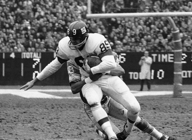"In this Dec. 10, 1967, file photo, New York Giants' Bob Crespino (89) is tackled by Detroit Lions' Tom Vaughn (48) after taking a pass from quarterback Fran Tarkenton for a first down in the first period of an NFL football game at Yankee Stadium in New York. A star at Ole Miss and a first-round pick in the 1961 NFL draft, Crespino played eight years as a split end in Cleveland and New York. But in his late 50s, Bobby Crespino also began developing vague neurological symptoms. His left leg became ""absolutely inflexible,"" his son Joe Crespino said."