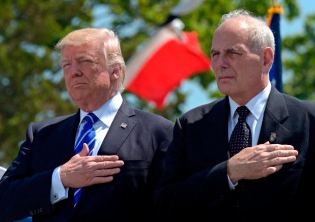 President Donald Trump and Homeland Security Secretary John Kelly listen to the national anthem during commencement exercises at the U.S. Coast Guard Academy in New London, Conn., on May 17. Trump has since appointed Kelly as his chief of staff.