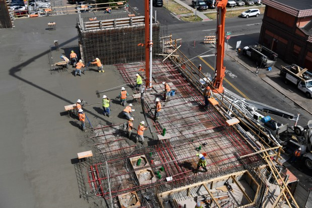 Concrete workers pour a concrete floor ...