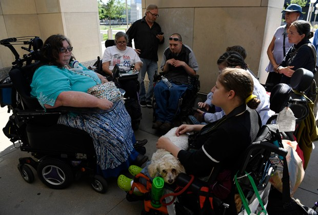 Carrie Ann Lucas, left, and other disabled protesters and supporters wait outside the Denver jail on June 30 for the release of at least eight protesters who were arrested at U.S. Sen. Cory Gardner's office. The protesters had staged a 58-hour sit-in, demanding that Gardner pledge to oppose Senate Republicans' health care bill.