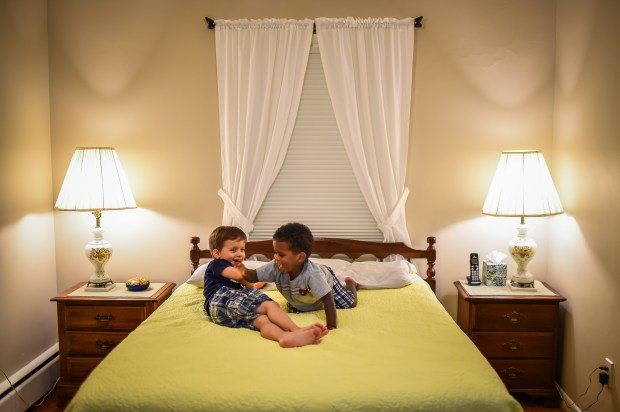 """Jimmy Isaacs, 4, left, and his brother, Joseph, 2, play on the bed inside the room that the family prepared to foster an """"unaccompanied minor refugee"""" from Africa."""