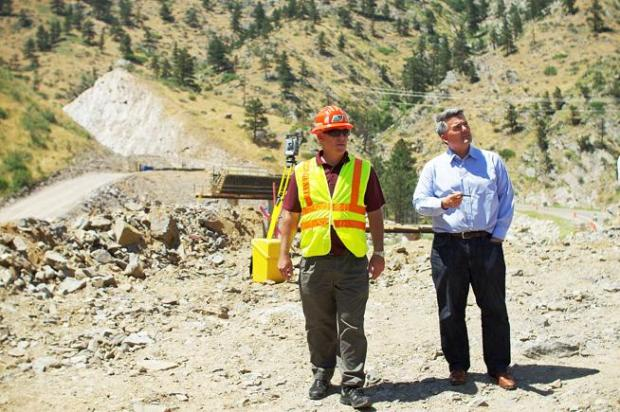 Johnny Olson, left, regional director for the Colorado Department of Transportation, talks Friday with Sen. Cory Gardner about changes to the roadway in the Big Thompson Canyon made in the wake of the 2013 flood. Behind them is the new roadway path to shortcut Horseshoe Bend.