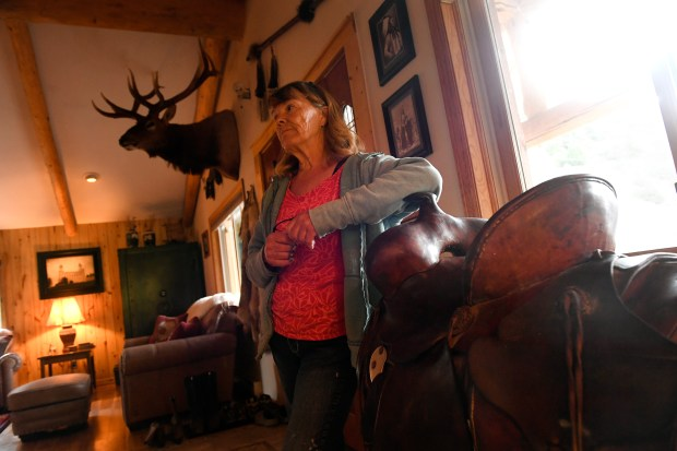 Longtime Colorado rancher Susan Robinson leans on the saddle belonging to her late-husband Larry inside her home on her ranch June 28, 2017 near Rifle.
