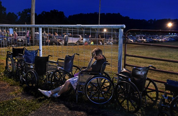 Josh Phillips waited all night, with hundreds of others, to get a chance to have dental work done. He rested in a wheelchair as he waited to be sent to a check-in area.