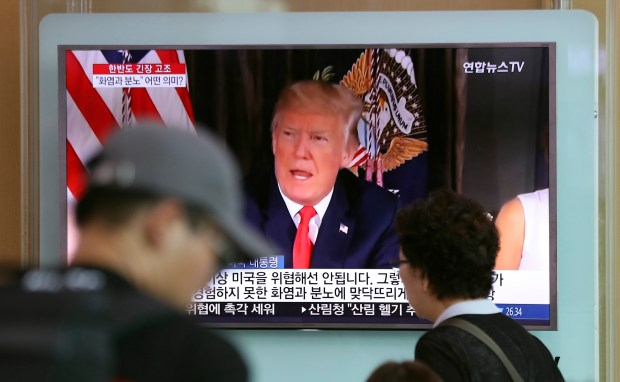 South Koreans walk past a TV screen showing an image of President Donald Trump speaking about North Korea on Wednesday in Seoul.