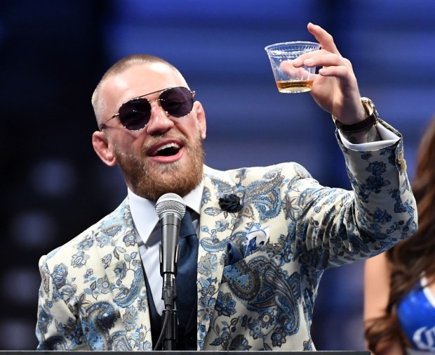 Conor McGregor holds up a drink ...